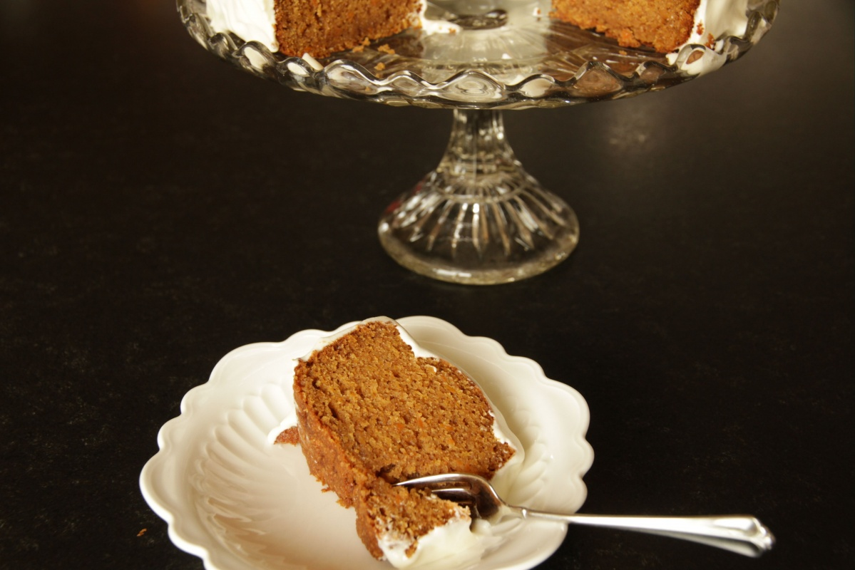Slice of carrot cake, cake on platter in background