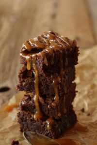 vertical stack of brownies with caramel sauce dripping down