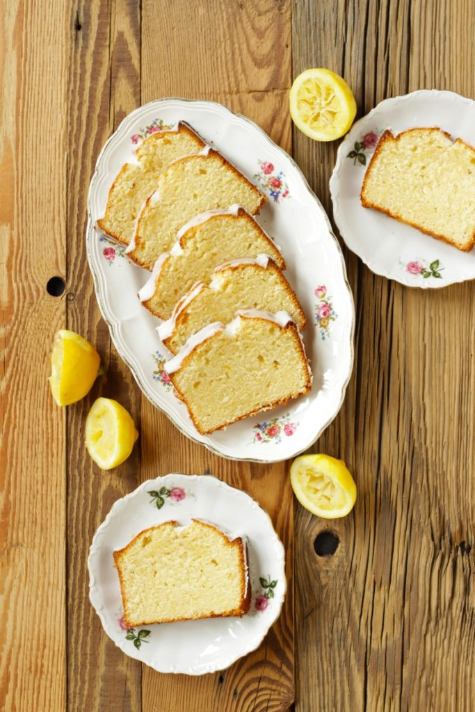 slices of lemon loaf cake on 3 white flowered plates on wooden surface viewed from above