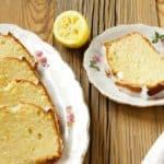 slices of lemon loaf cake on white plates on wooden surface
