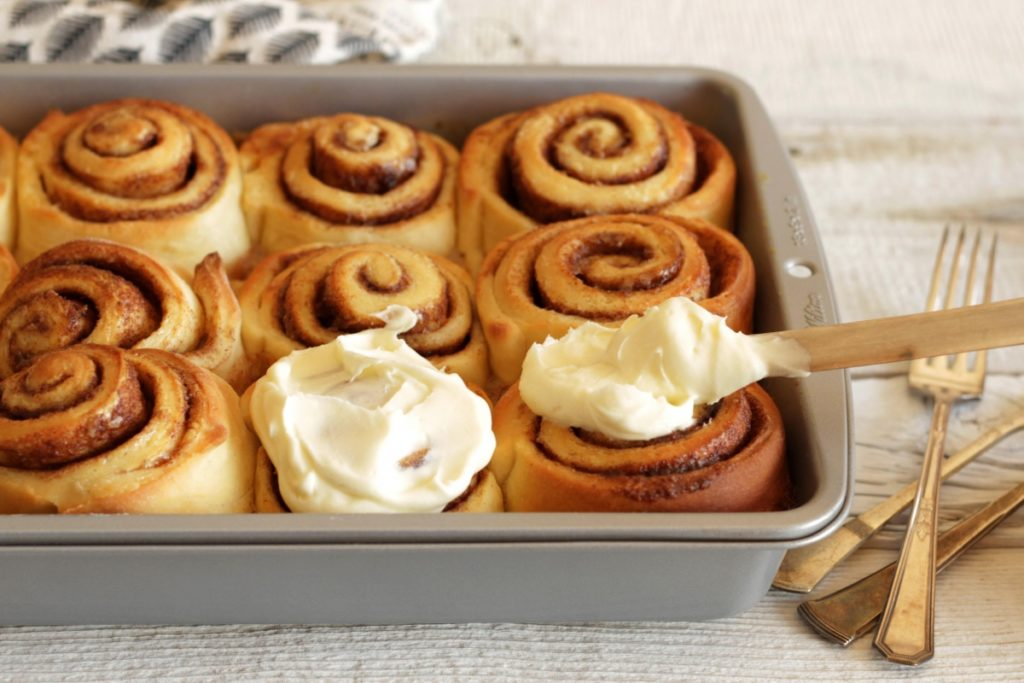 cinnamon rolls being frosted in pan