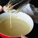 crêpe batter in bowl dripping from whisk