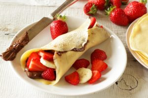 crêpes filled with nutella, strawberries and banana on plate